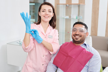 Portrait of pretty female dentist smiling at camera while posing with Middle-Eastern man sitting in patients chair, copy space