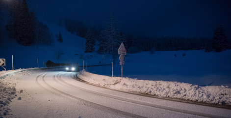 car driving on dangerous road at night on snow
