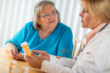 Female Doctor Talking with Senior Adult Woman About Medicine Prescription