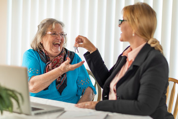Senior Adult Woman Getting House Keys From Real Estate Agent Near Laptop Computer