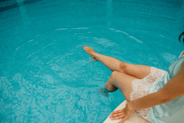 Woman sitting at the swimming pool, legs in water