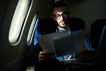 Portrait of successful young businessman working in dark plane while enjoying first class flight, copy space