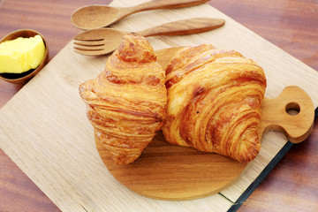 Croissant with butter on a wooden background.