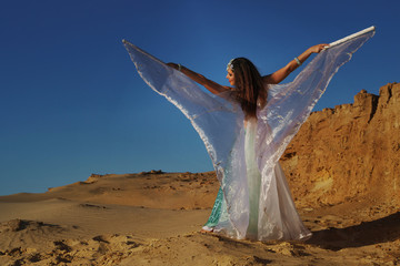 Oriental Beauty dancing belly dance with wings. Middle Eastern art. The girl in the desert. She waves her wings.
