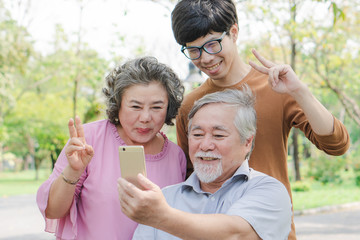 Happy elderly with family. Grandpa and grandma using mobile phone taking photo with grandson