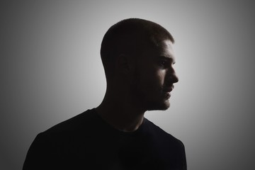 one young man, 20-25 years, moody dark portrait, profile. studio shot, gray background. head and shoulders shot.