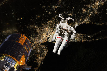 astronaut flying in open space over the USA during night, near earth. Image made of NASA photos f