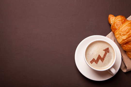 Cup of coffee with arrow up graph  on foam. Increased risks of growth in coffee consumption