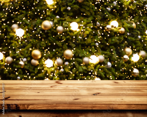 christmas and new year background with empty wooden deck table over blurred christmas tree at night