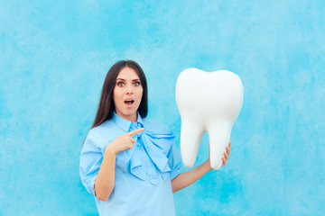 Funny Woman Holding Oversized Tooth in Dentist Concept Image