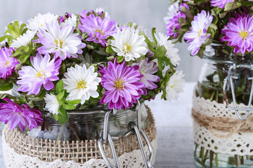 Bouquet of purple and white chrysanthemum flowers in glass jar