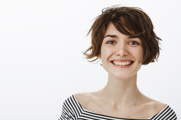 Close-up shot of friendly optimistic and happy european female coworker with stylish short haistyle, smiling joyfully and gazing at camera with pleased and satisfied expression, being proud of friend