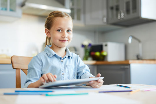 Little preschool child with tablet sitting in the kitchen and watching movie or other video