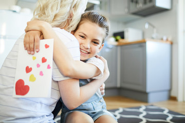 Smiling little girl with handmade greeting card embracing her mom in the kitchen