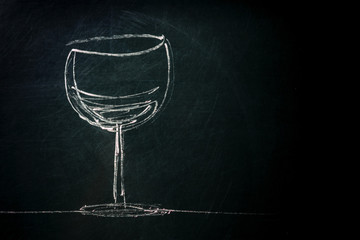A photo of a simple drawing of a glass of wine, made with chalk on a blackboard, with a place for text