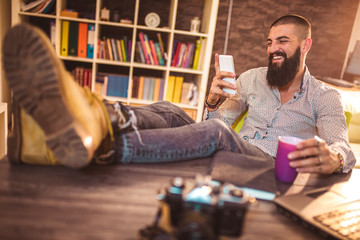 Portrait of modern young man relaxing in office with feet on desk texting via smartphone