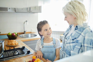 Cute little girl looking at her mom while helping her about the kitchen