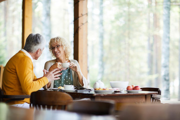 Obraz Positive beautiful mature couple in casual clothing sitting at table and drinking coffee at veranda while chatting in tranquil place - fototapety do salonu