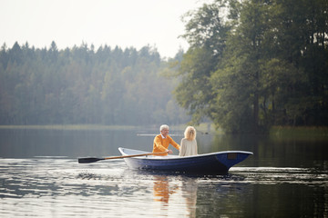 Happy senior couple in casual clothing sitting on boat and enjoying romantic date on lake, elderly man rowing oars
