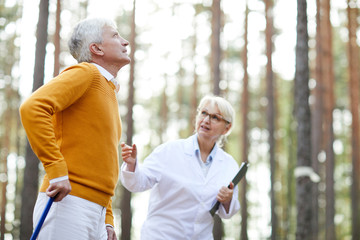 Rehabilitation specialist in glasses supporting senior patient and talking to him while they walking in forest, motivated senior man learning to walk after trauma