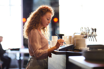 Serious pensive attractive curly-haired waitress standing at bar counter and using pencil while adding order in restaurant POS