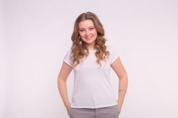 Fashion, style and people concept - pretty young woman dressed in white shirt over white background