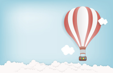 Hot air balloon in the sky with clouds and snowing. Origami paper art and digital craft style. Vector illustration