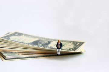 A miniature man reading a book sitting on the US dollar.