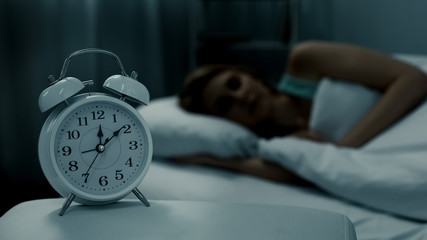 Young lady resting in her bed, midnight time shown on alarm clock, night dreams