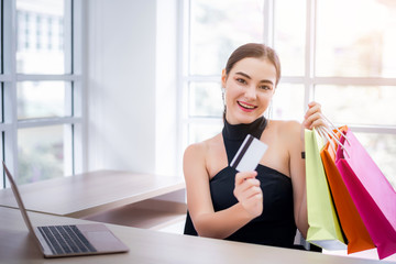 Attractive young businesswoman enjoy shopping online with full of bags with laptop and credit card at office. Have a colorful shopping bags hold on hand.