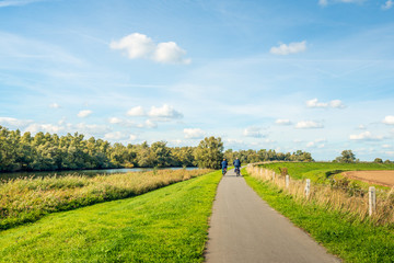 Elderly man and woman cycling on a bike path at the top of a dike at the edge of the Dutch National Park De Biesbosch