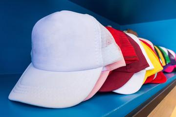 Obraz Colorful cap on blue shelf background. Fashion baseball or hiphop hat. - fototapety do salonu
