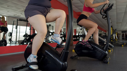Legs of plump and slim women pedaling on stationary bikes in gym, sport workout