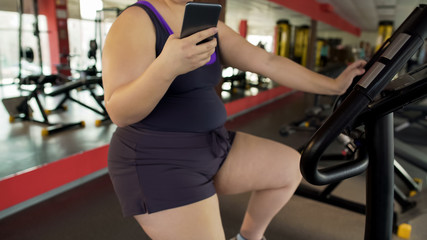 Plump female riding sluggishly exercise bike and watching video on cellphone