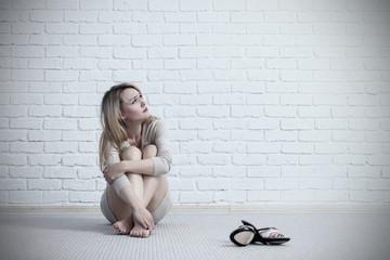 Young sad woman sitting on the floor near brick wall.