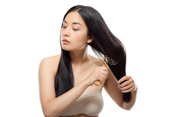 portrait of beautiful asian woman brushing hair isolated on white