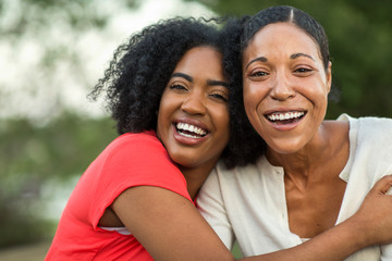 African American mother hugging her adult daughter.