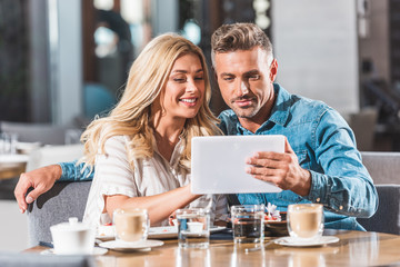 affectionate adult couple using tablet at table in cafe
