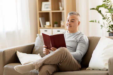 leisure, literature and people concept - man sitting on sofa and reading book at home
