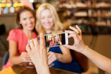 people, technology and lifestyle concept - woman photographing friends drinking wine by smartphone at bar or restaurant