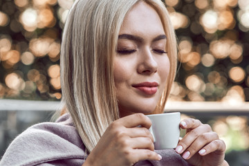 Young stylish blonde enjoys coffee