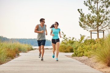 fitness, sport and lifestyle concept - happy couple in sports clothes and sunglasses running along summer beach path