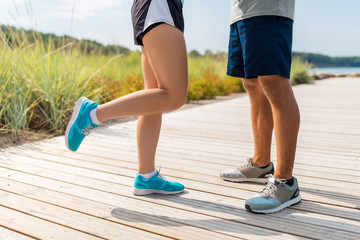fitness, sport and footwear concept - legs of couple of sportsmen in sneakers outdoors