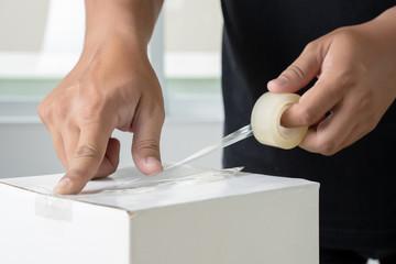 man hand transparent  man packing box adhesive tape.