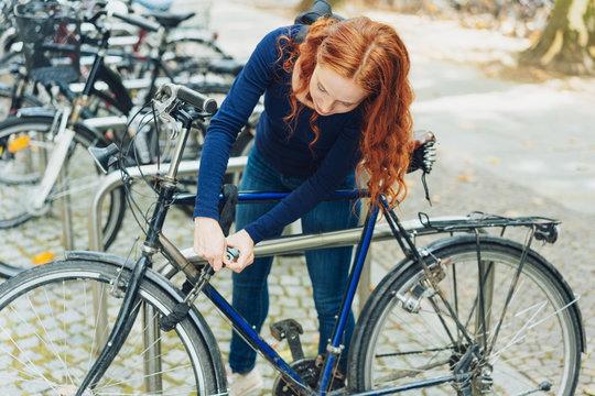 junge frau in der stadt schließt ihr fahrrad ab