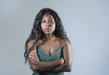 young beautiful and stressed black African American woman feeling upset and angry looking serious and pissed posing with folded arms on isolated studio background
