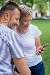 Couple in a park looking at a message on a mobile