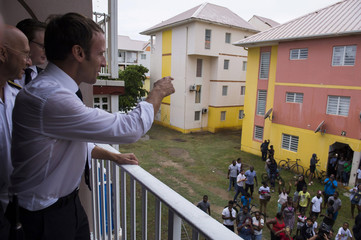 French President Emmanuel Macron reacts on a balcony as he meets residents in the Quartier Orleans during a visit to the French Caribbean island of Saint-Martin
