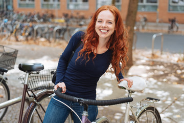 Smiling happy young student with her bicycle