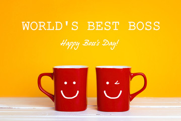 Boss day greeting card with two red coffee mugs with a smiling faces on a yellow background.
